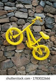 Yellow decorative bikes hanging on a stone wall