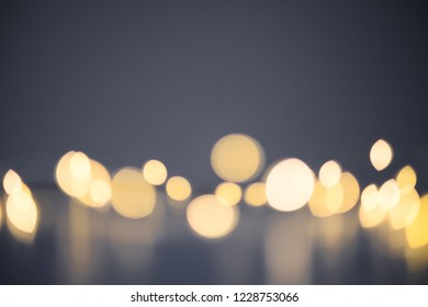 Yellow defocused light on dark background. Bright bokeh and space above.