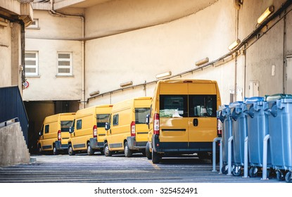 Yellow delivery vans in a row service van, trucks and cars in front of the entrance of a warehouse distribution logistic plant