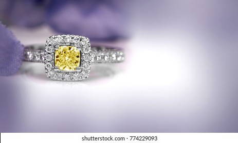 Yellow diamond ring with out focus color flower background