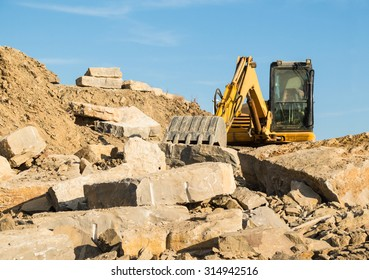 A yellow digger on a construction site building a stone wall with large slabs, blocks of lime stone.