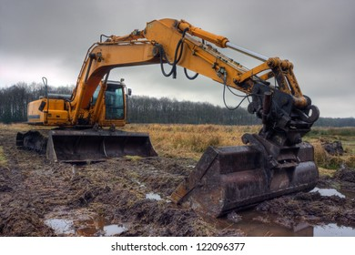 Yellow digger on a muddy site under a dark sky