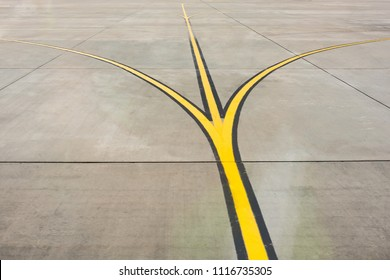 Yellow direction strips fork close up on an airfield runway