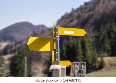 Yellow directional sign post on hiking path in Switzerland