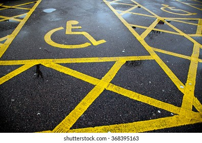 Yellow disable parking road sign marking on tarmac