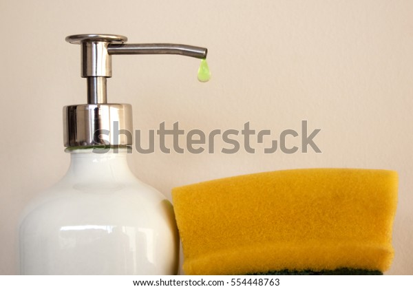 Yellow dish sponge with a drop of dishwashing detergent and bottle of dishwashing detergent