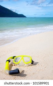 Yellow diving mask on the beach by the blue sea
