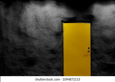 Yellow door with black wall with shadows and light. Copy space.