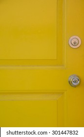 Yellow door with steel knob and deadbolt lock, background
