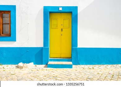 Yellow door in traditional portuguese house painted on blue and white, Tavira, Algarve