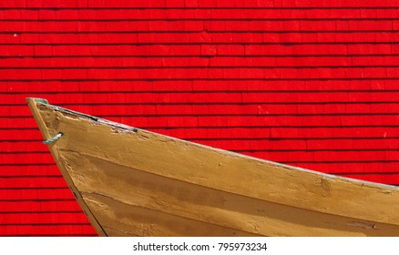 A yellow dory fishing boat with a red background