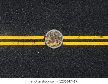 Yellow double solid line with the hatch cover. Road markings on asphalt on the street of Manhattan in New York City. Words NYC sewer on the hatch cover