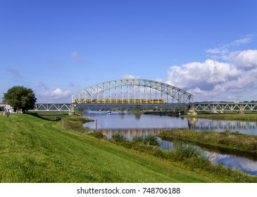 Yellow double-decker passenger train crossing the bridge over the river Rhine on a beautiful afternoon