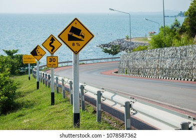 Yellow Downhill Caution Signs with Beautiful Road Background
