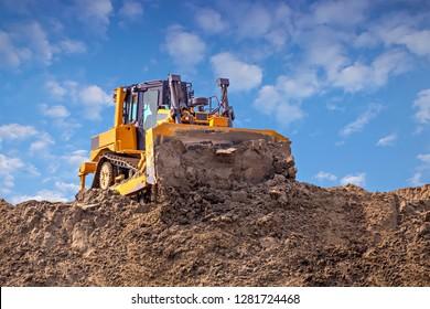 Yellow dozer pushes a pile of sand. Bulldozer working working on sand dune.