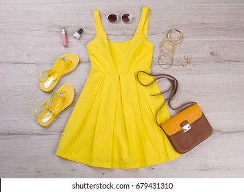 Yellow dress with accessories on a wooden background. Set of things for the summer. Summer vacation.