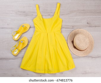 Yellow dress with sandals and hat. Beach summer clothes.
