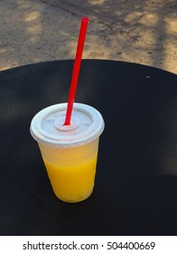 Yellow drink in a transparent plastic cup with cover and a red straw on a black round table