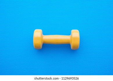 Yellow dumbbell for fitness exercise on blue yoga mat background in fitness center - Health care concept