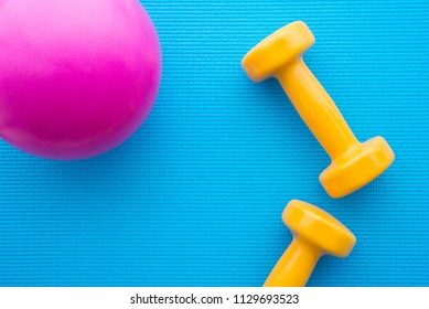 Yellow dumbbells and gym ball for fitness exercise on blue yoga mat background in fitness center - Health care concept