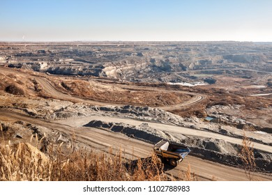 Yellow dump truck moving by the road to coal mine