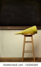 Yellow dunce hat on stool with chalkboard in background