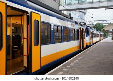 Yellow Dutch train on the Amsterdam Centraal station platform in morning. Centraal is the largest railway station of Amsterdam, Netherlands and a major national railway hub.