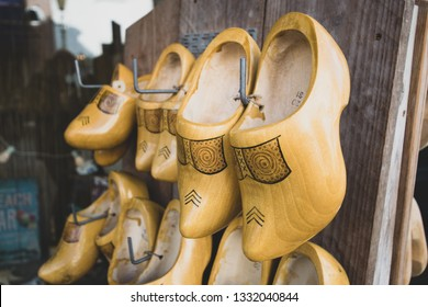 Yellow Dutch wooden clogs hang on a rack. Dutch tradition. Farmers' clogs. Old costume of The Netherlands.