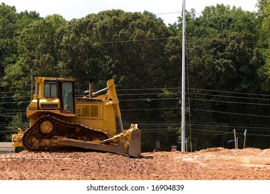 A yellow earth mover on a field of dirt