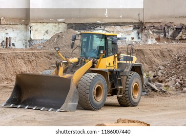 Yellow earth mover at an urban construction site
