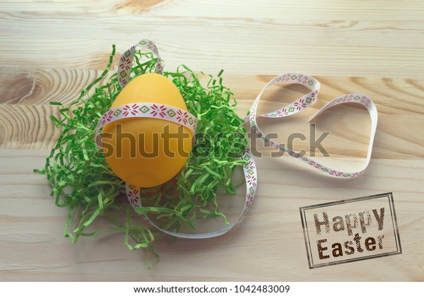 yellow egg in braid on wooden background with happy easter wishes