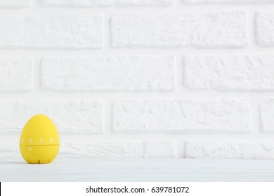 Yellow egg timer on a brick wall background
