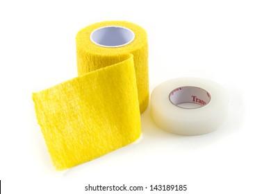 Yellow Elastic Medical Bandage and adhesive tape on White Background