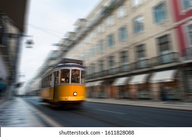 Yellow electric tram drive fast on old streets and colorful buildings of Lisbon, Portugal, digital motion blur.