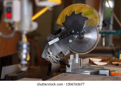 The yellow electrical circular mitre saw on the crafting table in the carpenter workroom. Soft focus.