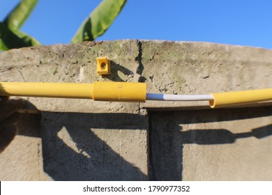 Yellow electrical conduit, White electrical wires and pipe clips are installed on the fence wall.