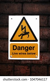 A yellow electrical danger sign on a red brick wall