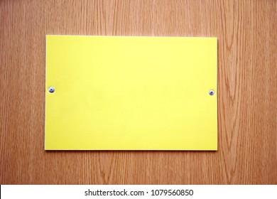 Yellow empty plate. Screwed to the wooden door with screws.