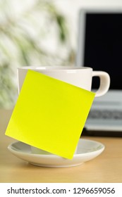 Yellow empty sticky note on white coffee or tea cup with copy space in front of laptop on brown wooden desk in office - selective focus