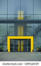 Yellow entrance of a modern glass office building