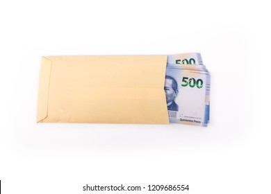 Yellow envelope full of Mexican 500 peso bills in one shot from above on white background