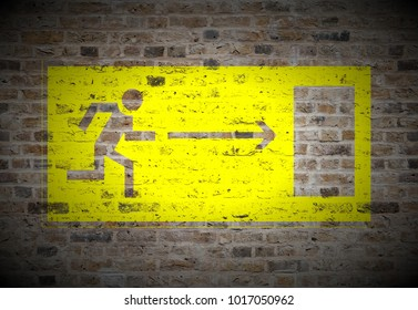 yellow evacuation door sign painted on biege sand brick wall texture background