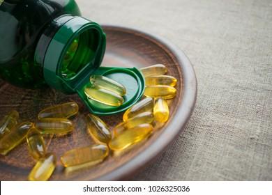 Yellow evening primrose seed oil gelatine capsules and green bottle on clay plate on burlap background. Evening Primrose Oil Softgels. Cis-Linoleic Acid, fatty acids,  Gamma-Linolenic Acid (GLA)