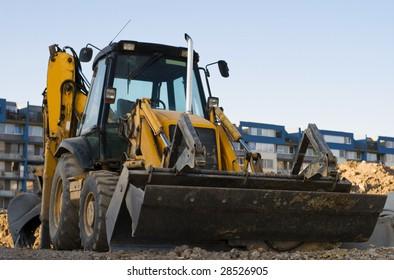 Yellow excavator with a backhoe