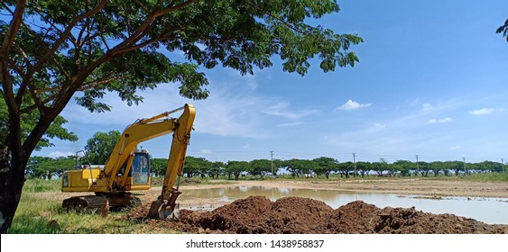 Yellow excavator (Backhoe) at work to make a drainage with a clear blue sky.