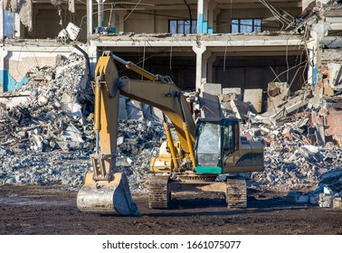 Yellow excavator with bucket at demolition of tall building. Hydraulic machine for demolish. Backhoe destroys concrete of the old structures on construction site