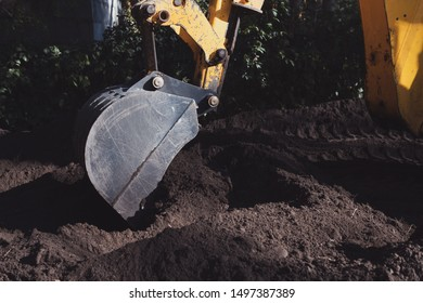 Yellow excavator bucket is digging a hole in the black ground on sunny day. Construction machinery during work.