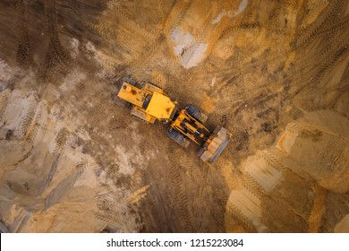 Yellow excavator or bulldozer works on construction site with sand, aerial or top view
