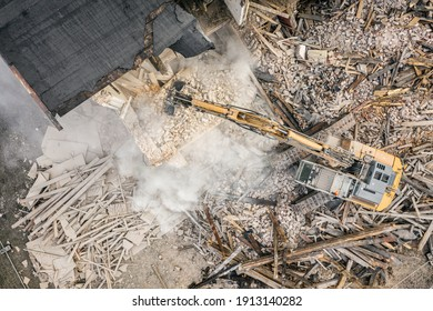 Yellow excavator destroys building. Heavy duty machine is demolishing a brick building. Demolition of the building . Demolition construction work aerial drone photo