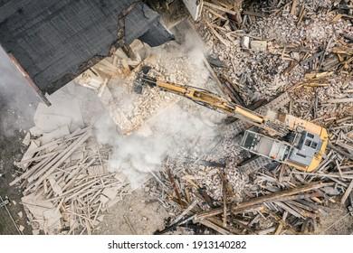 Yellow excavator destroys building. Heavy duty machine is demolishing a brick building. Demolition of the building . Demolition construction work aerial drone photo